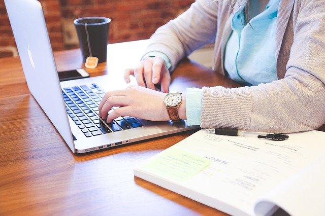eine Frau, die an einem Laptop arbeitet mit einem offenen Buch daneben